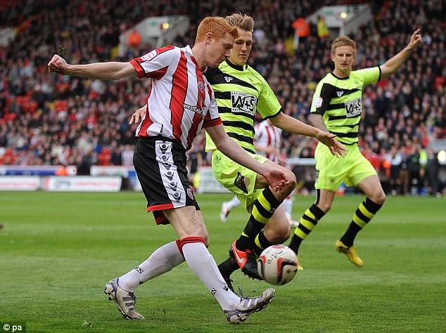 Challenge: Dave Kitson crosses the ball under pressure from Yeovil's Dan Burn