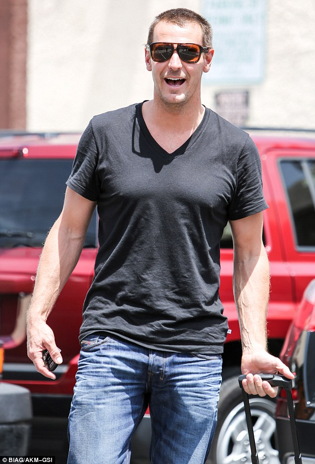 Irresistible: Ingo Rademacher looked cool and casual in jeans and black T-shirt, and smartly toted his things in a carry-on with wheels