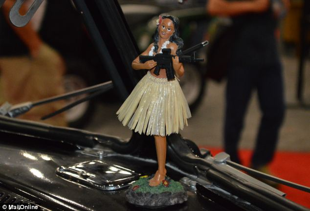 Only in Texas? Yes, it's a rifle-packing hula girl, and she's next to a dashboard-mounted ashtray of a 1962 VW microbus. Atop the vehicle sits a Dillon Aerospace machine gun