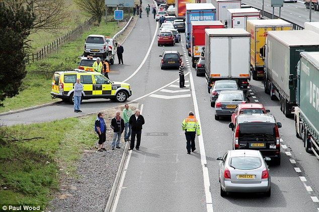 Going nowhere fast: Stranded drivers got out of their cars on the motorway this morning