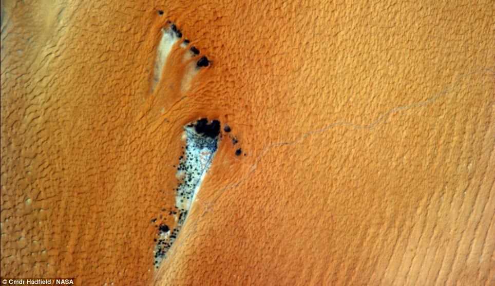 'In the lee of the rock - protecting an island of humanity in a sea of orange sand.' Some of the pictures look as if they are from a different planet