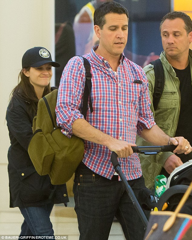 Back to the West Coast: Reese followed husband Jim Toth out of the airport, her tiny frame hiding behind his