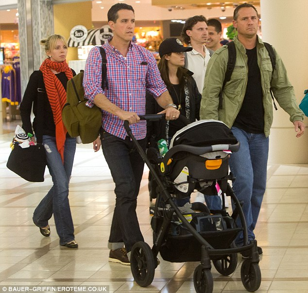 Incognito: Reese tucked behind her husband, who was pushing baby Tennessee, and friends to safely exit LAX