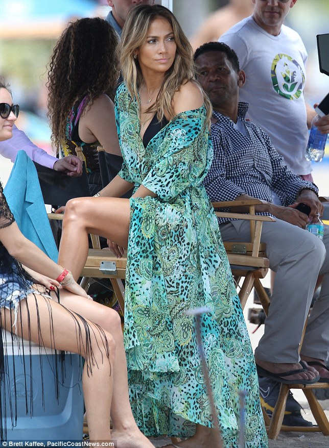 Showing off her legs: J Lo adjusts her dress between takes