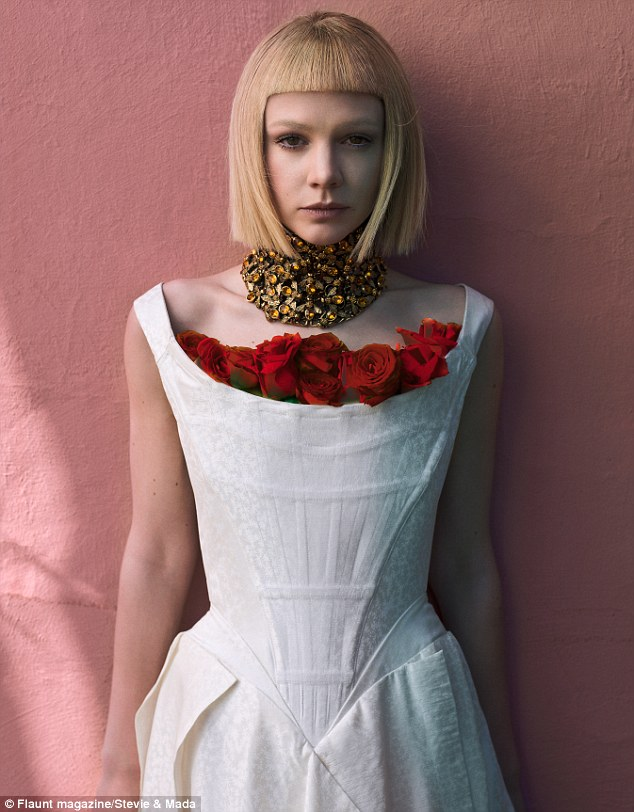 The white stuff: Carey sported a structured white dress with a bosom of red roses and distinctive choker