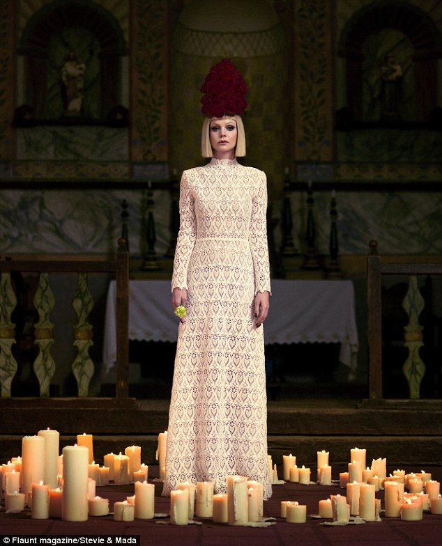 High drama: One striking shot shows the actress surrounded by lit candles with an alter in the background and a dramatic hat of crimson roses