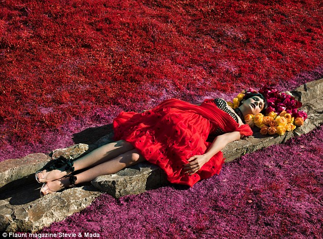 Field of flowers: Carey sported a flouncy red dress and sandals, complete with black and cream brassiere, and black wig