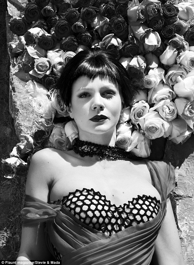 Coming up roses: Carey looked almost unrecognisable in a black wig and dramatic make-up in one vampish shot