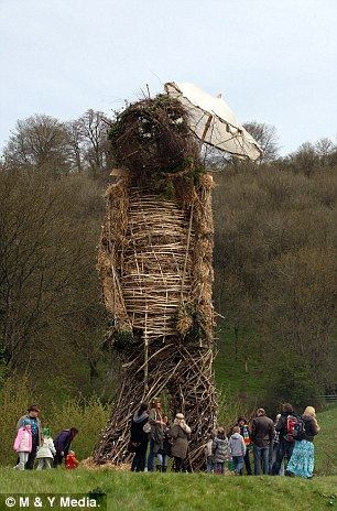 A huge 30ft Wickerman is inspected by visitors to Butser Ancient Farm, the reconstructed Iron-Age village of Butser near Petersfield, Hampshire