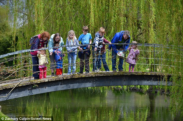 Families in Hampshire enjoy a game of Pooh sticks - a game described in the Winnie-the-Pooh books -  at the picturesque Mottisfont Abbey