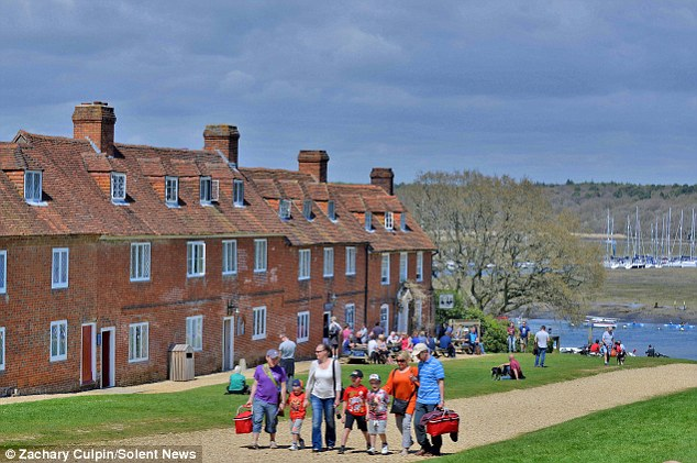 Family day out: Families enjoy the picturesque scene at the historic Bucklers' Hard in the New Forest National Park
