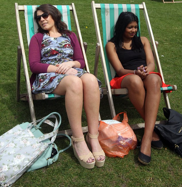 All decked out: Florence Kings, 23, pictured left, and Jo Phillips, 22, enjoy the warm bank holiday weather in Hyde Park, London
