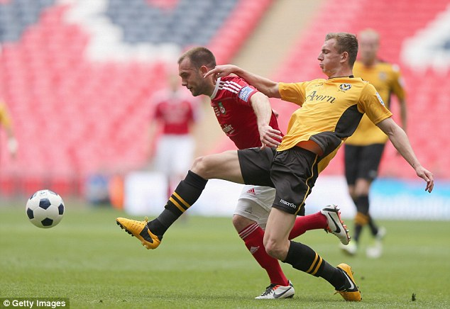 Strong challenge: Newport's Alex Gilbey pokes the ball away from Wrexham's Neil Ashton