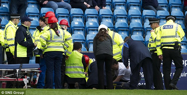 The emergency services treat a fan in the crowd who fell ill during the match