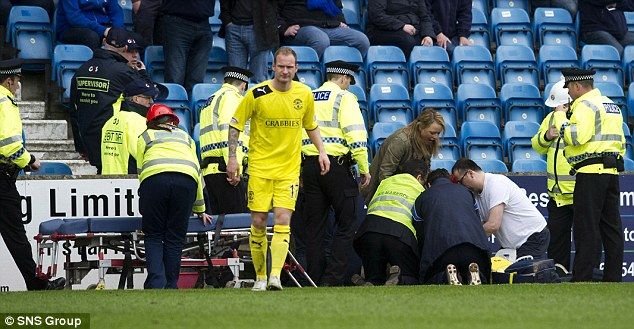 Emergency: Medics and police give first aid to a supporter taken ill with a 'suspected heart attack' at the Scottish Premier League match between Kilmarnock and Hibernian at Rugby Park