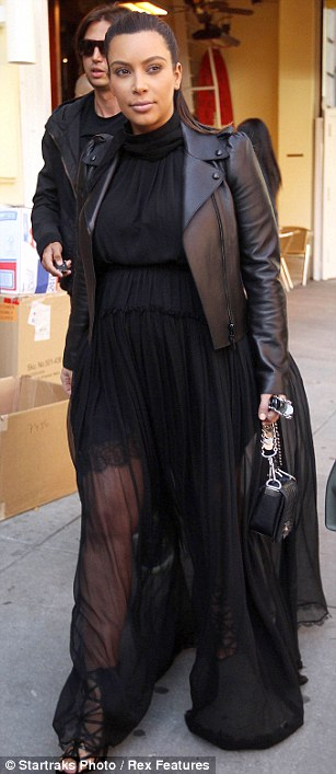 Woman in black: Kim has experimented with pregnancy fashion by alternately exposing and covering her growing bump