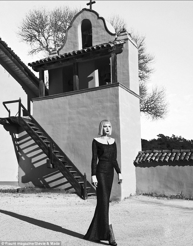 Black and white delight: The star looked almost gothic in her high collared long black dress with studded boots