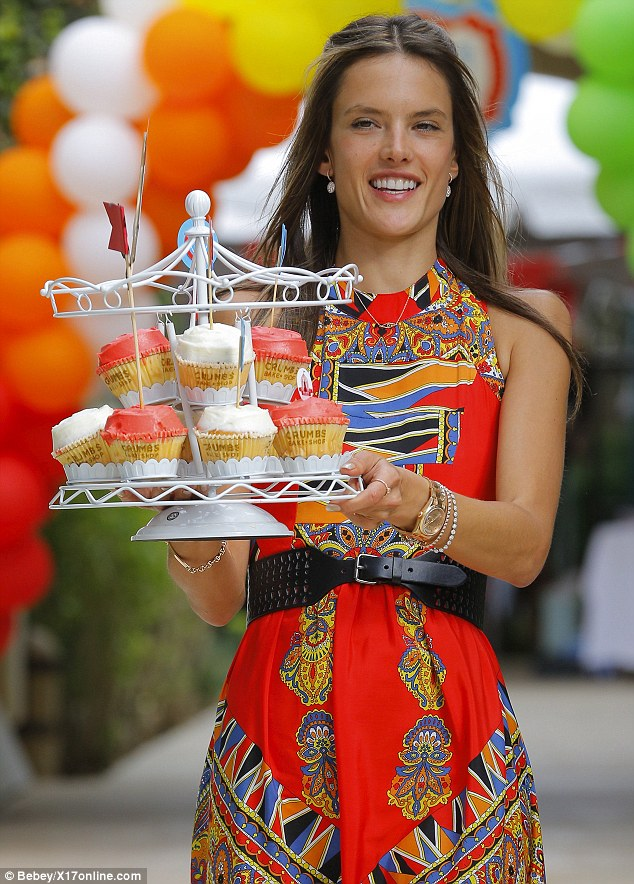 Anyone for cake? Alessandra carries a platter of cupcakes which matched her dress' bright tones