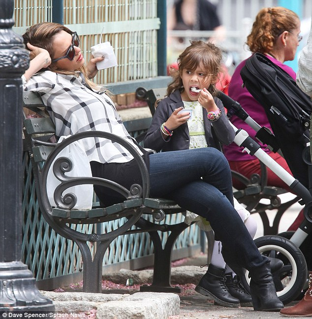 Time to rest: Jessica relaxed on a park bench while daughter Honor enjoyed a snack