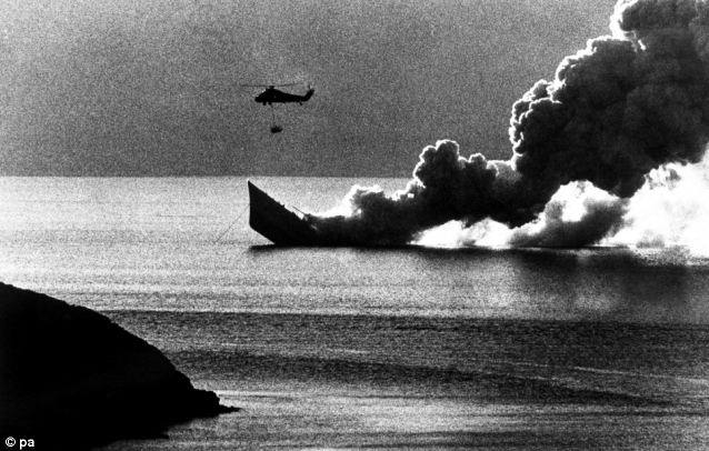 Conflict: A helicopter hovers overhead as HMS Antelope, still burning fiercely, slips beneath the water of Ajax Bay. The ship was hit by Argentine air attack, and sank after an unexploded bomb went off during an attempt to defuse it