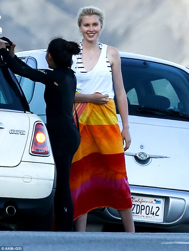 Painting the beach red (and orange and yellow): Ireland Baldwin grins as she steps off the beach wearing a bright stripey towel