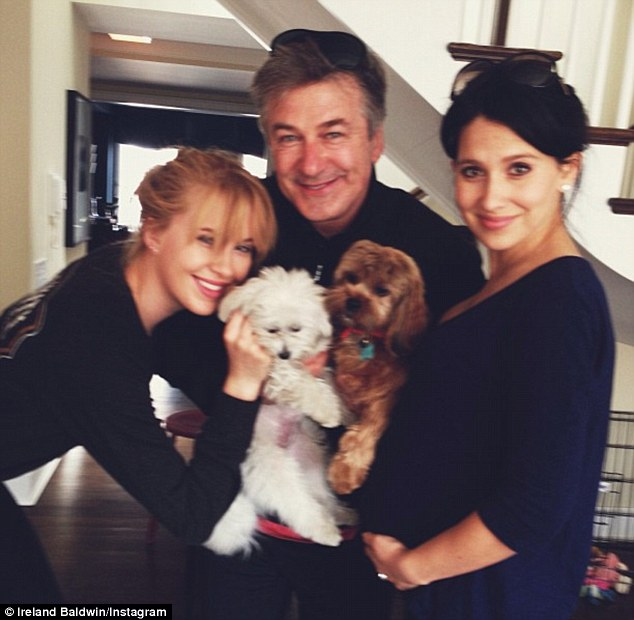 Happy families: After her chilled out day of fun on the beach, Ireland then spent time with her father Alec Baldwin and his pregnant girlfriend Hilaria - as well as their beloved pooches