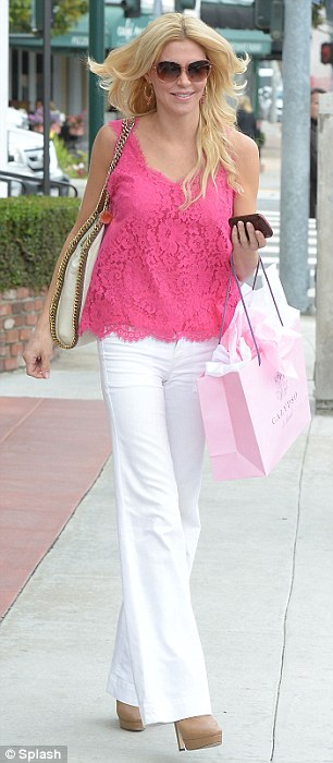 Not blending in: Brandi made sure to stand out in white flared pants and a bright pink top when she went shopping at Calypso Boutique