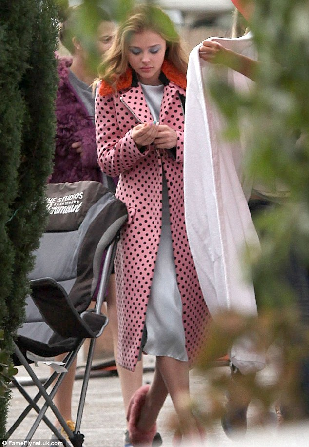 Pretty in pink: The teen star wore a polka dot trench coat for a change in costume