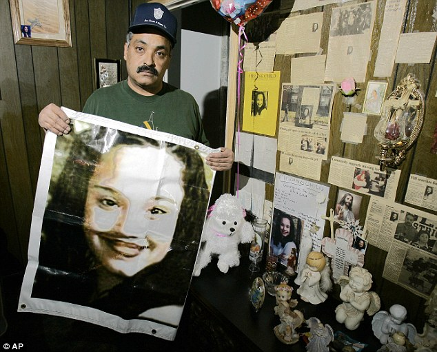 Hope: Felix DeJesus, holding a banner showing his daughter's photograph, standing by a memorial in his living room in Cleveland in 2004