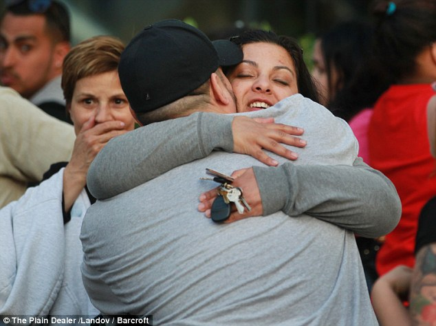 Relief: Two people hug outside the hospital . Crowds of Cleveland residents gathered at the police station and cheered as squad cars pulled into the station Monday night