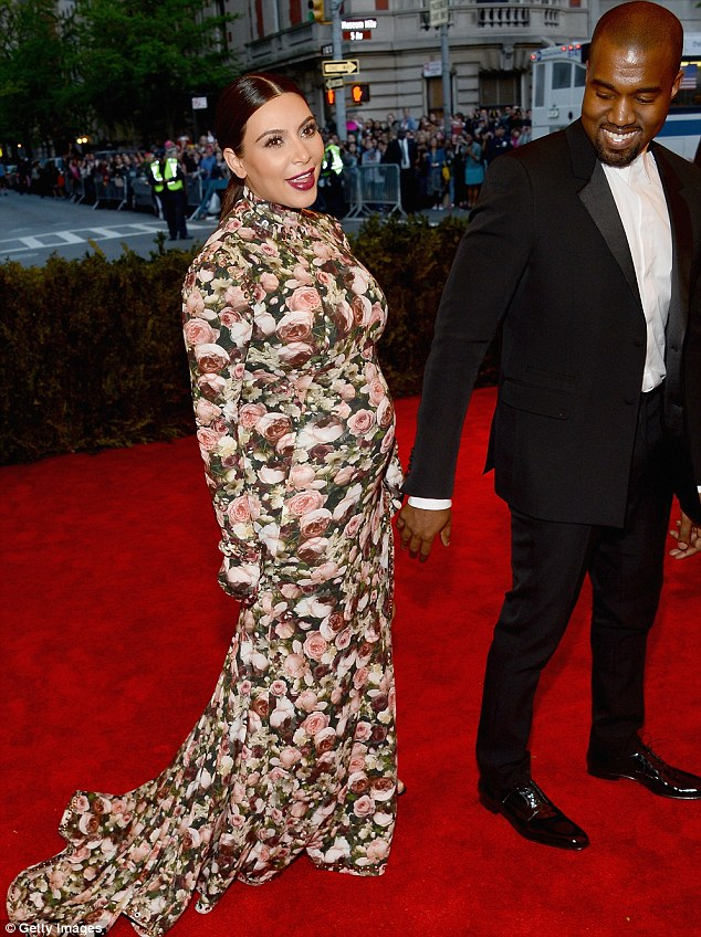 A rare smile: The usually glum Kanye looked happy as he reaches for Kim's hand on the carpet