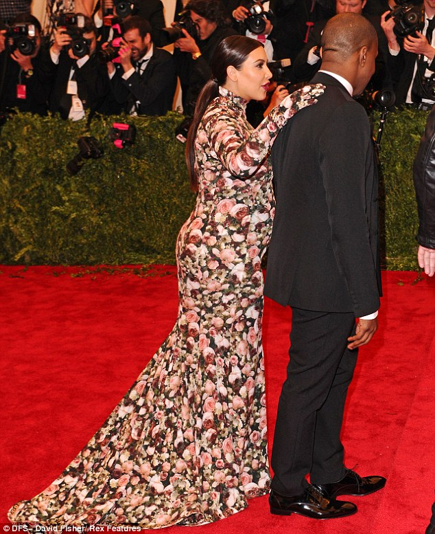 That's my man: Kim places a possessive hand on Kanye's shoulder as she is escorted into the ball