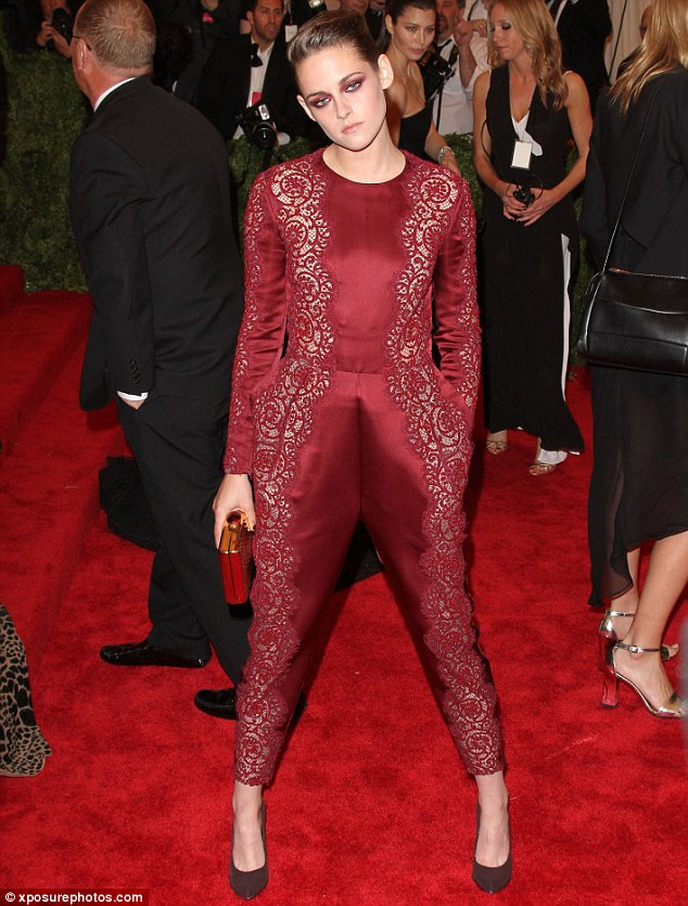 Scarlet woman: Kristen adopted a somewhat unusual pose as she showcased her silk Stella McCartney jumpsuit on the red carpet