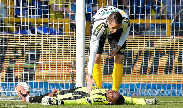 Knocked out: Lokeren's Boubacar Barry lies injured on the ground after hitting the post