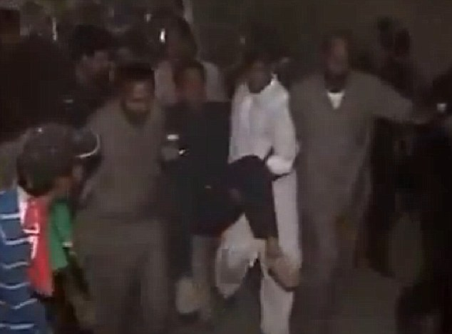 Knocked out: Imran Khan appears to be unconscious as he is carried away from the rally in Gulberg, near Ghalib market, in the eatern city of Lahore