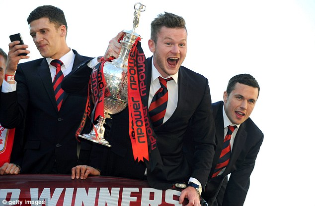 Victory parade: Mark Hudson, Aron Gunnarsson and Don Cowie celebrate Cardiff's promotion from the bus