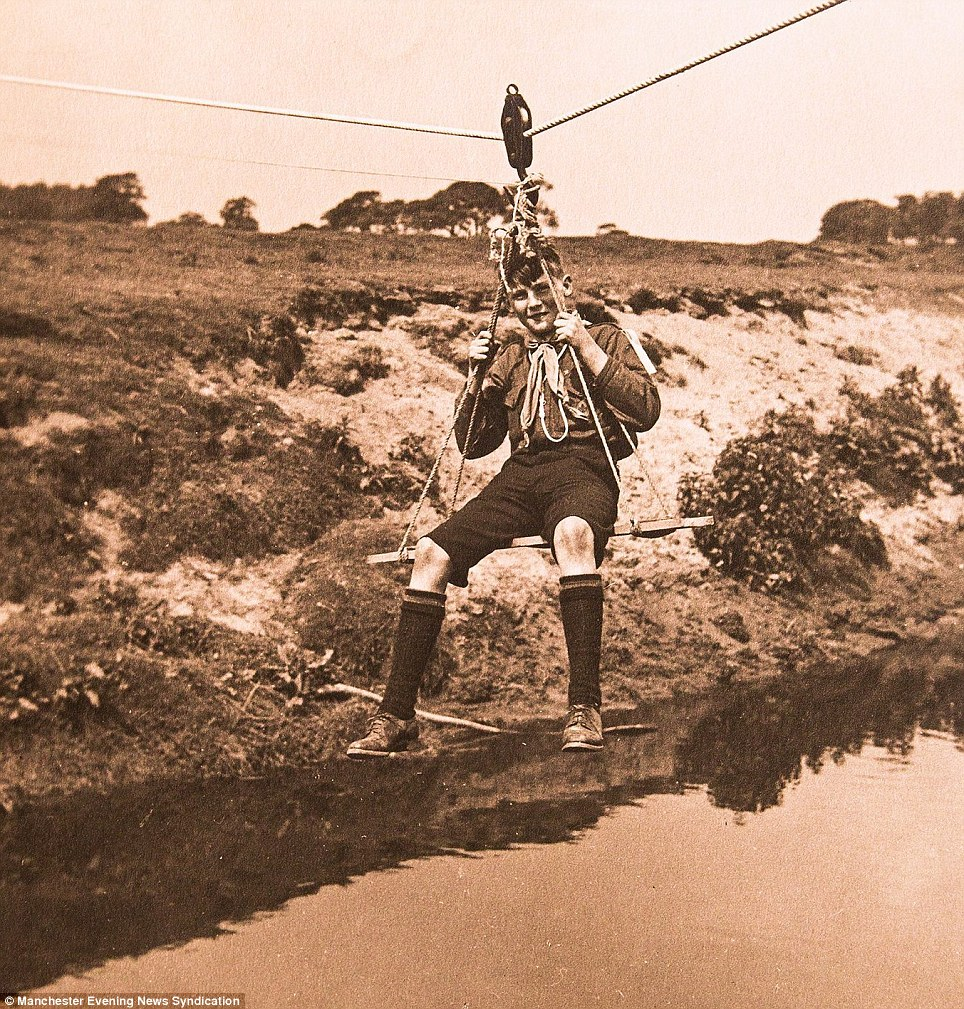 A young scout dangles from an improvised rope bridge, which looks a lot like a plank attached to some lengths of rope
