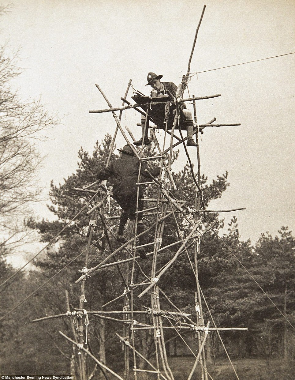 In another shot, a scout perches on top of an alarmingly rickety tower, cobbled together from wooden poles, while a boy clambers his way up