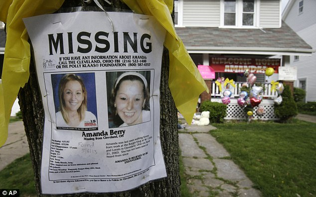 Long journey: A missing poster still rests on a tree outside the home of Amanda Berry on Wednesday in Cleveland