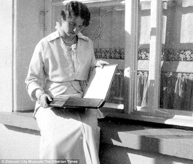 Grand Duchess Olga is seen looking through a family album - a neat twist to the newly-discovered photographs of the Romanovs