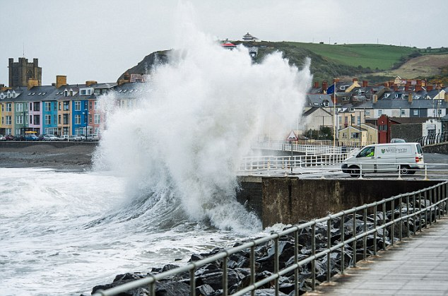 Battering: Despite basking in glorious sunshine, Britain will face winds of up to 60mph and driving rain today. This picture shows huge waves crashing over the promenade at Aberystwyth on the west Wales coast