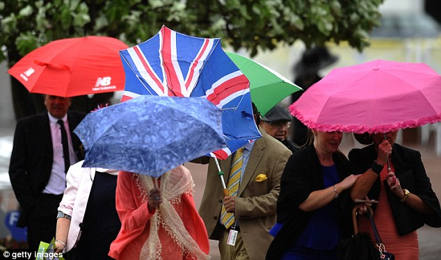 Protection: The umbrellas were out in force at a wet and windy Chester racecourse today