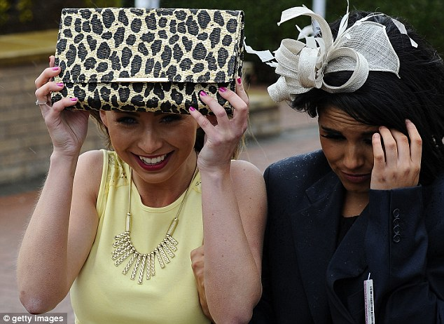 Going's wet: A racegoer shelters under her handbag during the rainy weather at Chester