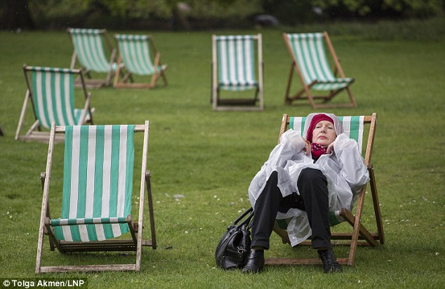 Downtime: A woman rests on a deckchair under the rain in St James's Park in London