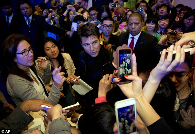 Surrounded: Tom appeared every inch the movie star as he greeted fans following his arrival in Beijing