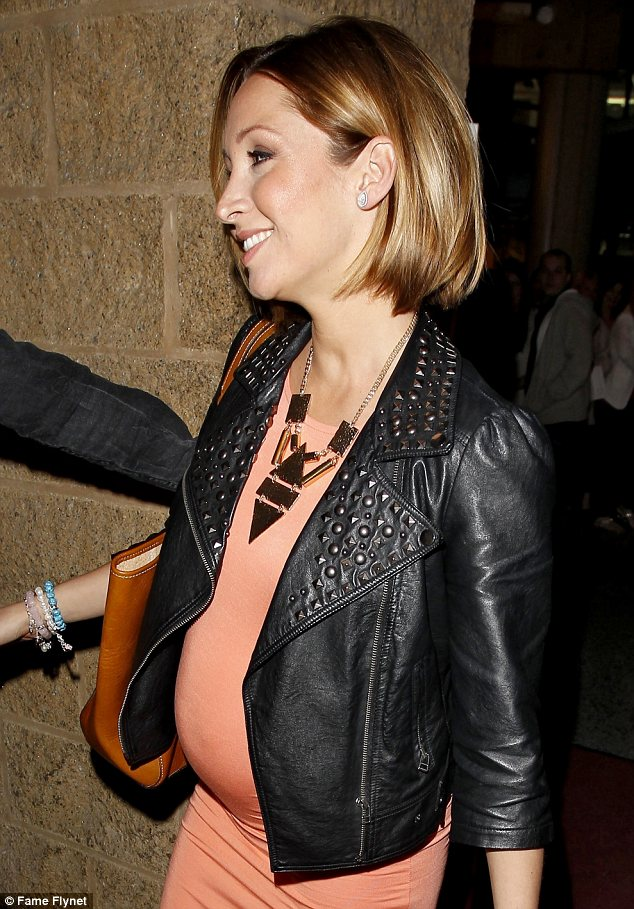 In full bloom: Lucy-Jo Hudson showed off her pregnant frame in a bright orange dress as she stepped out to attend the Beyoncé in Manchester on Thursday night