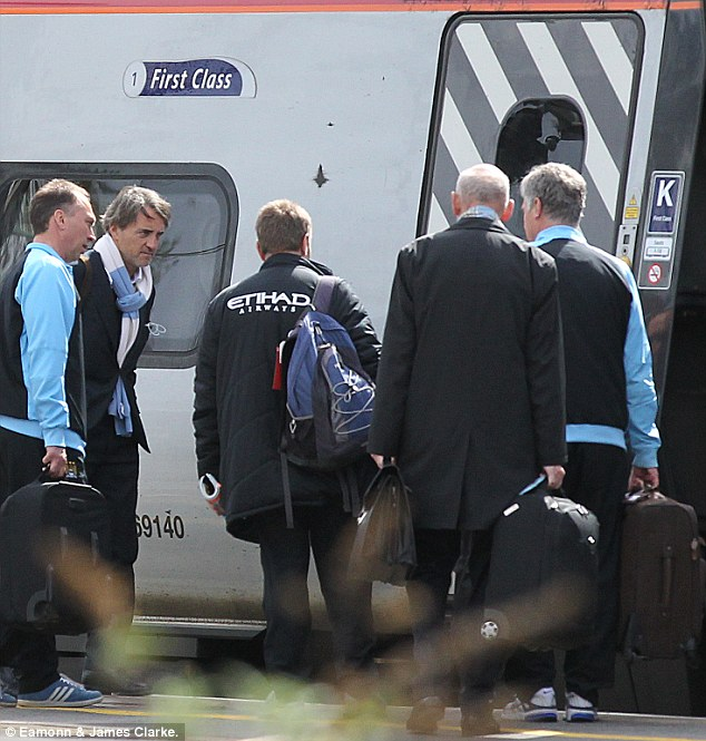All aboard: Mancini boards the train with assistants David Platt (left) and Brian Kidd (right)