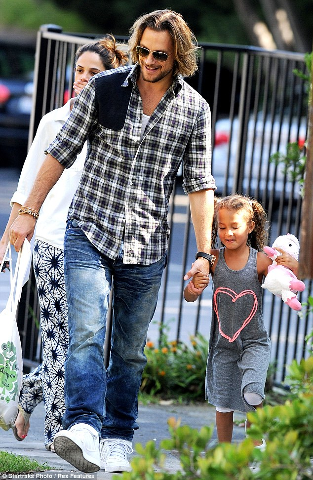 Pure joy: The five-year-old held on tightly to her father's hand as she skipped along beside him