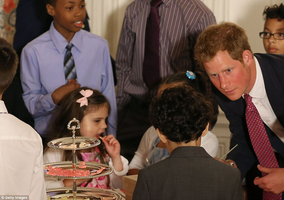 Having a chat: Prince Harry talks to young children during an event hosted by Michelle Obama