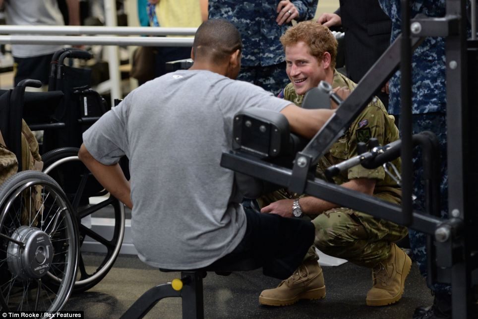 Tour: Prince Harry chats with a wounded serviceman as he is shown around the Walter Reid Memorial Center in Maryland on Friday morning